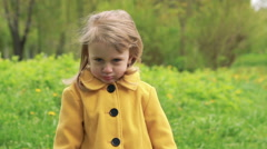 Little girl showing dandelion on a camera. Slowly - stock footage