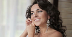 Happy bride herself puts her earrings on the ears - stock footage