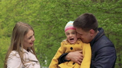 Little girl on a parents arms grimacing on a camera. Slowly - stock footage