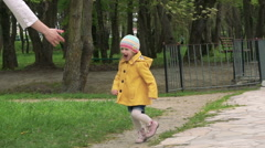 Little three years old girl running to mother and smiling. Slowly Stock Footage