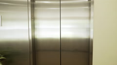 elevator doors open and woman walks out past camera 4k - stock footage