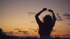 Silhouette of woman dancing at sunset Stock Footage