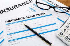 Insurance claim form with pen and calculator on wood desk Stock Photos