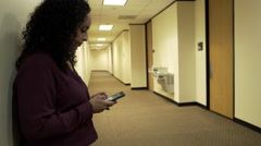 Businesswoman standing in hallway of office building using her cell phone Stock Footage