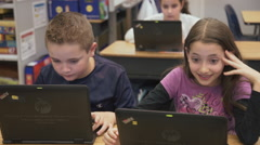 Good looking kids on the computer smlling Stock Footage