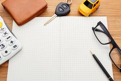 Car key with calculator pocket money and pen on blank notebook - stock photo