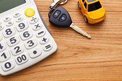 Car key with calculator on wood table - stock photo