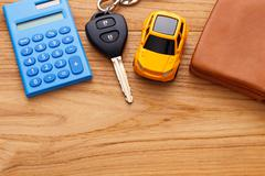 Car key with calculator on wood table background - stock photo