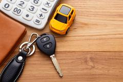 Car key with calculator and pocket money on wood table background Stock Photos