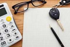 Car key on blank notebook with calculator and pen on wood table - stock photo