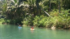 Two girls floating in boats on the river in the jungle. Stock Footage