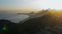 Flying above Copacabana Beach with sunset rays above the mountains Stock Footage