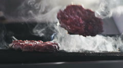 Burger on a grill at commercial kitchen of restaurant. Slow motion Arkistovideo