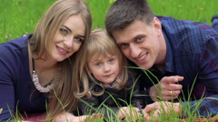 Close up portrait of young parents and little girl resting on grass. Slowly - stock footage