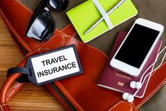 Travel bag with insurance tag and tourist accessories - stock photo