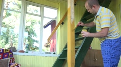 Man paint yellow colour wooden column near stairs to loft. 4K Stock Footage