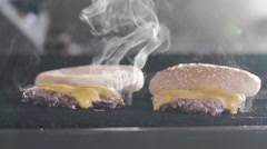 Burger on a grill at commercial kitchen of restaurant. Slow motion - stock footage