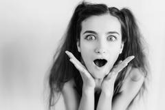 Surprised young girl with pigtails - stock photo