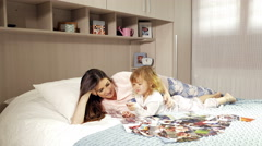 Young mother with daughter looking pictures of family lying in bed 4K Stock Footage