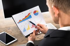 Young Close-up Of A Businessman Analyzing Graph At Desk In Office - stock photo