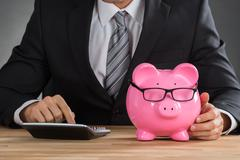 Close-up Of Businessman Using Calculator To Calculate With Piggybank On Desk Stock Photos