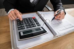 Close-up Of Male Accountant Calculating Tax At Desk In Office Stock Photos