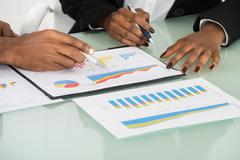 Close-up Of Businesspeople Analyzed By Graphs And Charts At Workplace Stock Photos