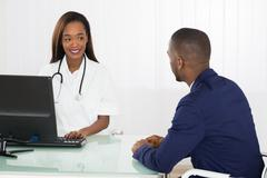 African American Doctor And Patient Discussing On Computer At Diagnostic Cent - stock photo