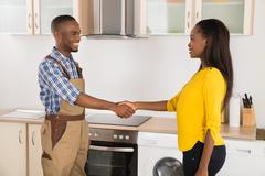 Young Serviceman And Woman Handshaking In Kitchen Stock Photos