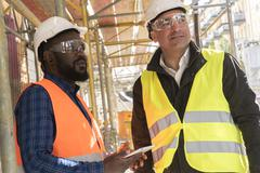 A black and a white construction workers among scaffolding on construction site Stock Photos