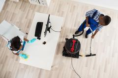 High Angle View Of Male And Female Janitor Cleaning Office With Vacuum Cleane Stock Photos