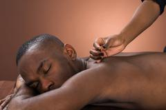 Young African Man Getting Acupuncture Treatment In Spa Stock Photos