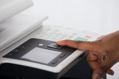 Close-up Of Young Businesswoman Hand Pressing Printer's Button In Office - stock photo
