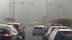 Cars stop on road intersection with red traffic lights in thick smog. 4K Stock Footage