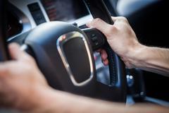 Hands on steering wheel - stock photo