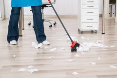 Close-up Of A Janitor Sweeping Torn Paper Pieces On Hardwood Floor - stock photo