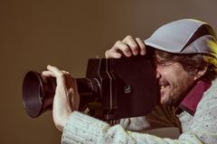 man wearing a cap with an old movie camera - stock photo