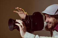 Portrait of cheerful man with a beard makes movies - stock photo
