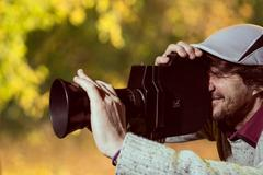 man wearing a cap with an old movie camera. - stock photo