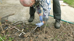 Senior elderly man plumbs water pipes in garden Stock Footage