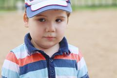 Closeup of little handsome boy in cap outdoor at summer, shallow dof Stock Photos