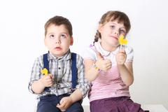Little boy and girl sit and hold lollipops in studio, girl thumbs up - stock photo