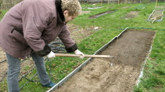 Country girl ploughs plows a bed vegetable garden Stock Footage