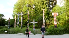 People taking picture in front of native totem poles Stock Footage