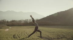 Woman exercising yoga in Greek nature,grass field,tall trees Stock Footage