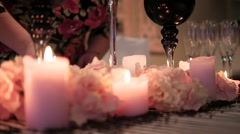 decorated table with candles and decorations. A woman lights a candle - stock footage