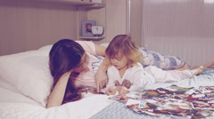 Young mother with daughter looking pictures of family lying in bed 4K vintage Stock Footage