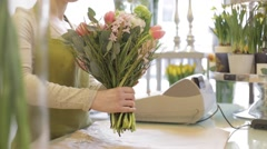 Florist wrapping flowers in paper at flower shop Stock Footage