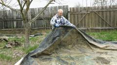 Elderly man prepares ground waterproof protection Stock Footage