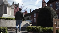 Mans walks past War Memorial in St Albans, UK Stock Footage